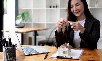 gros plan sur les clés, femme souriante agent immobilier vendant un appartement, offrant au client, montrant à la caméra, tenant des documents, contrat, concluant un accord d'achat, agent immobilier, hypothèque ou loyer photo