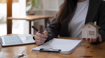 agent immobilier travaillant au bureau, examinant le contrat de location sur papier. consultant immobilier travaillant dans un bureau moderne. photo