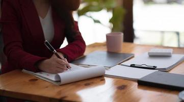femme comptable ou comptable fournissant un service de comptabilité pour les petites entreprises, tenant un stylo pour prendre des notes et utilisant une calculatrice, femme utilisant une tablette numérique et une calculatrice photo