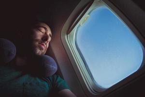 jeune homme avec oreiller cervical se reposant et dormant dans un avion photo