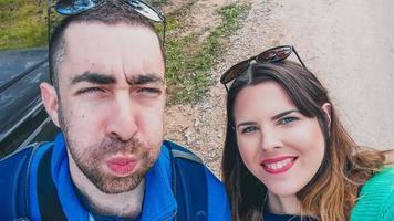 heureux jeune couple faisant des grimaces stupides et drôles tout en prenant une photo de selfie avec leur smartphone ou leur appareil photo dans le parc