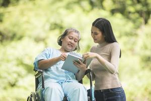 femme heureuse dans un fauteuil roulant lisant un livre avec sa fille au parc photo