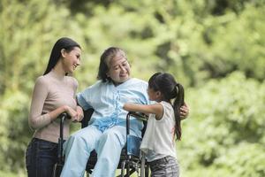 heureuse grand-mère en fauteuil roulant avec sa fille et son petit-enfant dans un parc, vie heureuse temps heureux. photo