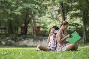 mère et fille lisant un conte de fées à sa fille écoutent le son avec un casque dans le parc photo