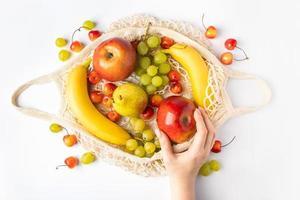 une femme met des fruits mûrs dans un sac en filet écologique pour faire du shopping. les mains des femmes tiennent un sac en coton avec des produits de la ferme biologique. mode de vie durable. photo