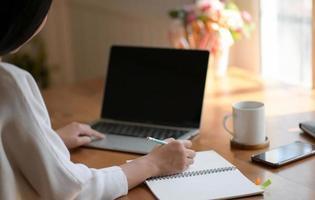 une jeune femme utilise un ordinateur portable et rédige un rapport. elle travaille à domicile. photo