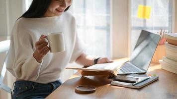 une photo d'un jeune étudiant tenant une tasse de café et lisant dans un beau café lumineux.