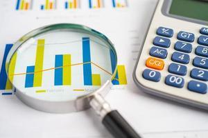 loupe et calculatrice sur papier graphique. développement financier, compte bancaire, statistiques, économie de données de recherche analytique d'investissement, négociation en bourse, concept de bureau d'affaires. photo