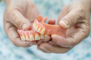 patiente asiatique âgée ou âgée tenant une prothèse dentaire dans un hôpital de soins infirmiers, concept médical solide et sain photo