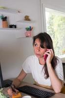 femme adulte caucasienne travaillant à la maison, utilisant un téléphone portable et prenant des notes. photo