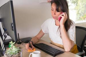 femme adulte caucasienne travaillant à la maison. prendre des notes et utiliser son téléphone de contact photo