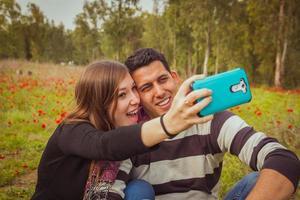 couple prenant selfie photo avec leur téléphone portable dans le champ de coquelicots rouges