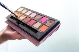 gros plan des mains de femme tenant une palette d'ombres à paupières maquillage coloré photo