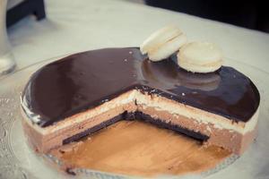 gâteau mousse chocolat-vanille avec glsaz de chocolat et deux macarons blancs photo