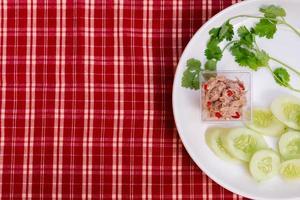 salade épicée avec mini thon et tranches de coriandre et de concombre sur une assiette blanche. fond de tissu rouge, vichy. photo
