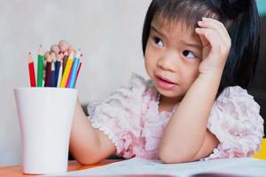la fille était assise et écoutait les adultes lui enseigner ses devoirs et elle jouait la couleur du bois dans le verre blanc. les enfants étaient intrigués par les instructions. photo