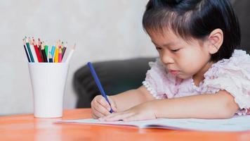 petite fille dessinant à la maison le développement de la créativité, détail des mains d'un jeune enfant dessinant à colorier avec des crayons multicolores. photo
