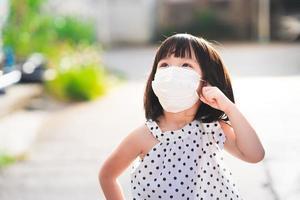 une jolie fille portant un masque facial hygiénique blanc se dresse en levant les yeux. les enfants réfléchissent et se demandent ce qu'ils voient le matin. photo