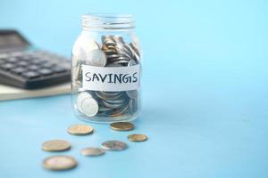 économiser le pot de pièces et la calculatrice sur la table photo