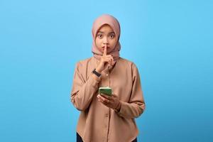 portrait de jeune femme asiatique tenant un téléphone portable et fait un geste de silence avec les doigts photo