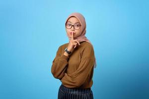 portrait de belle femme asiatique montrant un geste silencieux sur fond bleu photo
