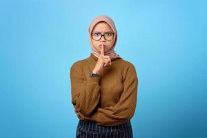 jolie jeune femme asiatique doigt sur les lèvres et faisant un geste silencieux sur fond bleu photo