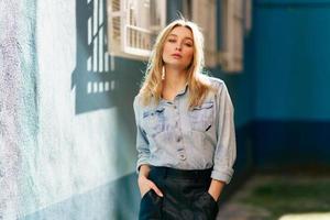 femme blonde portant une chemise en jean et une jupe en cuir noir debout dans la rue. photo