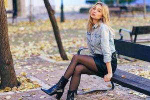 femme blonde portant une chemise en jean et une jupe en cuir noir assis dans un banc urbain. photo
