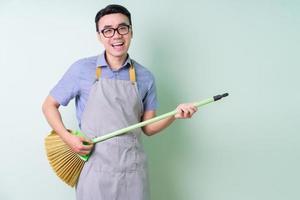jeune homme asiatique portant un tablier posant sur fond vert photo