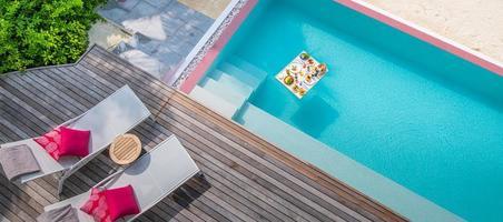 petit-déjeuner dans la piscine, petit-déjeuner flottant dans un luxueux complexe tropical. table de détente sur l'eau calme de la piscine, petit-déjeuner sain et assiette de fruits au bord de la piscine du complexe. mode de vie de luxe plage couple tropical photo