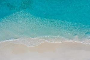 paysage marin d'été belles vagues, eau de mer bleue en journée ensoleillée. vue de dessus du drone. vue aérienne de la mer, fond de nature tropicale incroyable. belle mer lumineuse avec des vagues éclaboussant et concept de sable de plage photo
