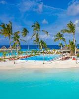 vue aérienne de dessus. luxueuses villas avec piscine sur la plage, bungalows palmiers et lagon océan bleu turquoise, horizon marin, jetée en bois, jetée. île d'été se détendre voyage et vacances idylliques photo