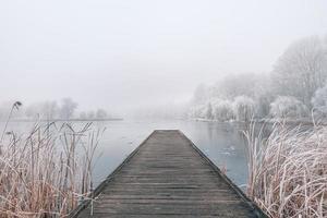 paysage d'hiver du soir. jetée en bois sur un magnifique lac gelé. arbres avec givre, paysages d'hiver saisonniers calmes. vue paisible et blanche photo