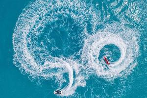 les gens jouent au jet ski dans la mer. vue aérienne. vue de dessus. fond de nature incroyable. sport de plein air de liberté fraîche. journée d'aventure. amusement de sports nautiques sur l'océan turquoise clair à la plage tropicale photo