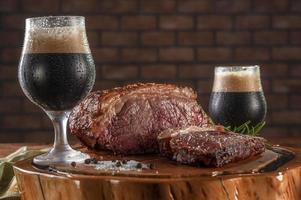 contre-filet grillé sur une planche à découper en bois avec deux verres de tulipe en sueur de bière pression noire. photo