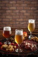 assiette froide avec de la bière pression sur une planche à découper en bois photo