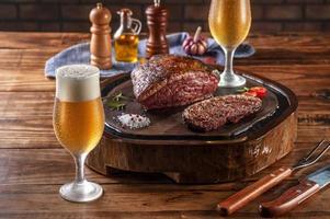 deux verres de bière tulipa froide en sueur avec un rumsteck tranché grillé sur une planche à découper en bois - picanha brésilien. photo