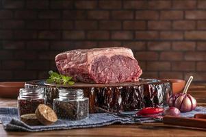 chorizo argentin de bœuf de contre-filet cru sur une planche à découper en résine de bois avec des épices. table en bois avec fond de mur de briques. photo