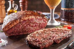 rumsteck tranché grillé avec deux verres de bière sur une planche à découper en bois. viande de boeuf en marbre - picanha brésilien. photo