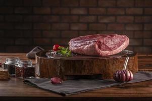 rumsteck cru de boeuf - picanha brésilien - sur une planche à découper en résine de bois avec des épices. table en bois avec fond de mur de briques. photo