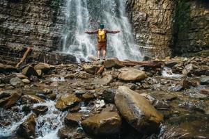 homme voyageur avec un sac à dos jaune debout sur fond d'une cascade photo