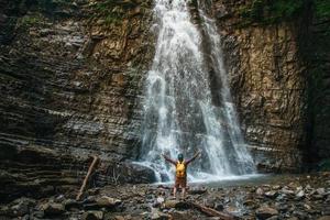 homme voyageur avec un sac à dos jaune debout sur fond d'une cascade. concept de mode de vie de voyage. photo