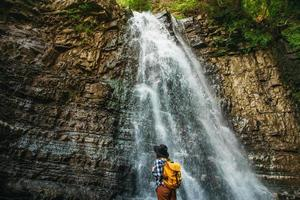 voyageur femme portant un chapeau et un sac à dos en se tenant debout contre une cascade photo