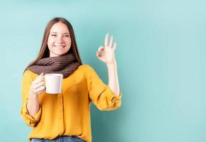 Jeune femme de race blanche portant un foulard buvant du café ou du thé montrant un signe ok sur fond bleu photo