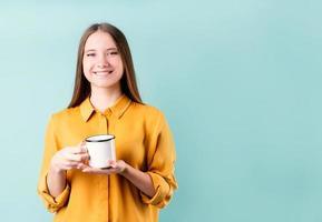 Young caucasian woman wearing a boire du café ou du thé sur fond bleu photo