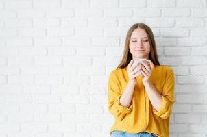 Jolie femme adolescente en chemise jaune buvant du thé photo