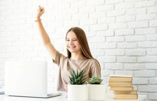 adolescente apprenant de la maison assise au bureau avec le bras levé photo