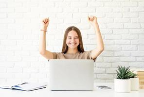 Adolescente apprenant à la maison assise au bureau avec les bras levés photo