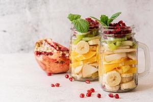 salade de fruits colorés dans un pot Mason sur fond de béton rustique vue de face photo