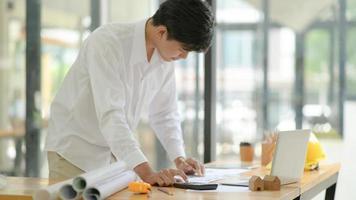 les architectes utilisent une calculatrice pour concevoir et planifier la construction de bâtiments pour les clients. photo